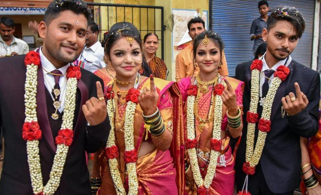 Two newly married couples show their ink-marked fingers after casting their votes for Karnataka Assembly elections in Hubbali on Saturday. PTI Photo