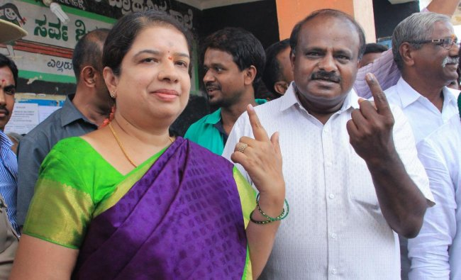 JD(S) State President H D Kumaraswamy and his wife Anitha Kumaraswamy show their inked fingers after casting their votes for the Karnataka Assembly elections in Ramnagar, Karnataka on Saturday. PTI Photo