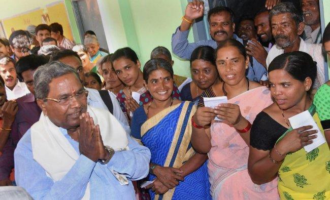 Karnataka Chief Minister Siddaramaiah greets his supporters after voting in the Karnataka Assembly elections 2018, at Hundi village in Mysore on Saturday. PTI Photo