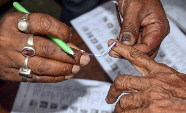 Polling officials put an ink mark on a voter\'s finger after during Panchayat Election at a polling booth in Howrah district of West Bengal on Monday. PTI Photo