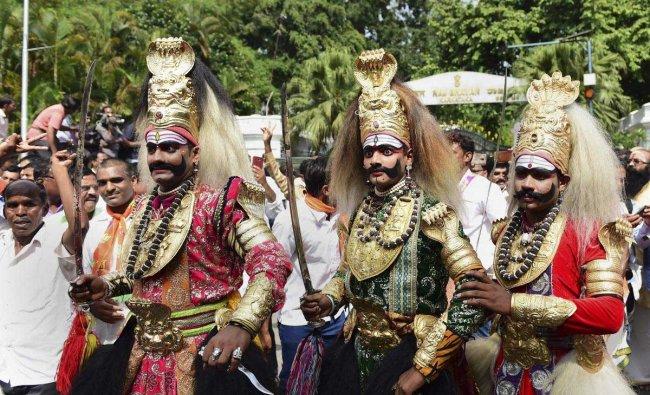 Folk artists join BJP supporters as they celebrate the swearing-in of new Karnataka Chief Minister B S Yeddyurappa, outside Raj Bhavan in Bengaluru, on Thursday. PTI Photo