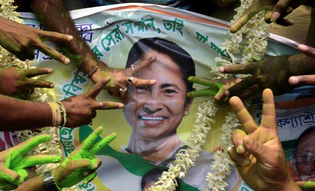 All India Trinamool Congress supporters celebrate with a poster of TMC Chief and West Bengal Chief Minister Mamata Banerjee to celebrate their win in Panchayat elections, in North 24 Parganas, on Thursday. PTI Photo