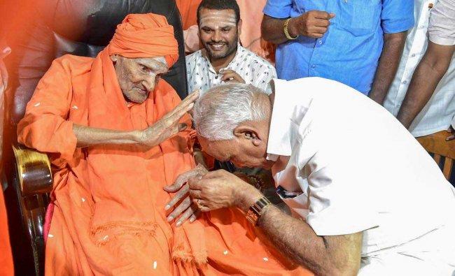 Newly-elected Karnataka chief minister BS Yeddyurappa seeks the blessings of Shivakumara Swami, at Sree Siddaganga Matha in Tumkur, on Thursday. PTI Photo