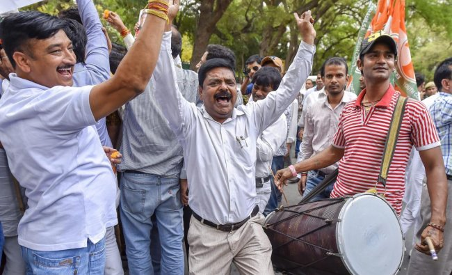 Congress party workers celebrate after Karnataka Chief Minister BS Yeddyurappa announced his resignation, in New Delhi on Saturday. PTI Photo