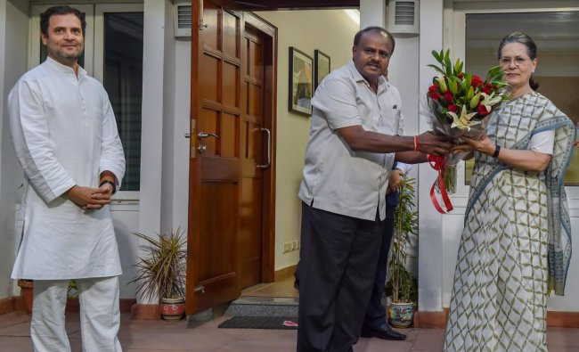 JD(S) leader and Karnataka chief minister-designate H D Kumaraswamy presents a bouquet to former Congress president Sonia Gandhi as Congress President Rahul Gandhi looks on during a meeting, at the latter\'s residence, in New Delhi. PTI Photo