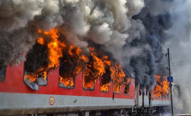 Smoke billows out of two bogies of the Andhra Pradesh AC Superfast Express which caught fire near Gwalior. PTI Photo