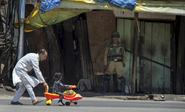 A child looks at a security personnel standing guard outside a shop, as his father pushes his toy car during restrictions in Srinagar. PTI Photo