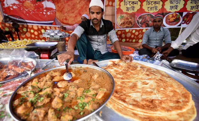 Vendors prepare delicacies at a roadside shop during the holy fasting month of Ramadan in Guwahati. Reuters Photo