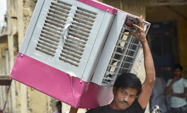 A worker carries an air cooler as temperature soars on a hot, summer day, in New Delhi. PTI Photo
