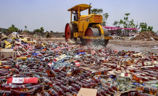 A road roller destroys a stock of illegal liquor at Kamdhenu ground, in Ahmedabad. PTI Photo