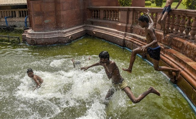 Children play at a water body near Vijay Chowk, during a hot day in New Delhi. PTI Photo