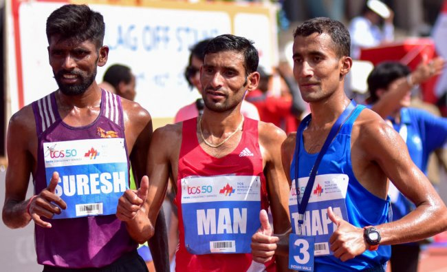 Suresh(Left) winner of the gold in TCS world 10 K run (elite Men INDIA) is seen with the first Runner up Man Singh(Centre) and the second runner up Thapa, at Sree Kanteerava Stadium, in Bengaluru on Sunday.DH Photo