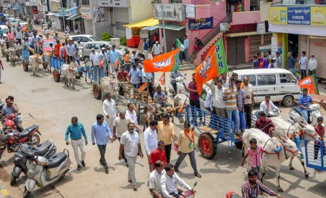 Chikmakalur: BJP workers stage a bullock-cart rally protest during their Karnataka bandh, called over the various issues of the farmers, in Chikmagalur on Monday, May, 28, 2018. (PTI Photo)