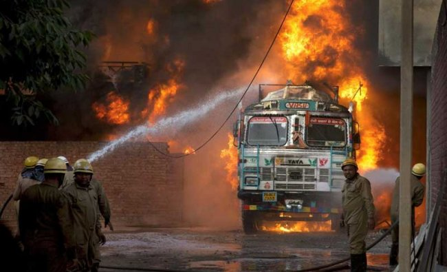 Firefighters douse flames on a truck which caught fire at Malviya Nagar in New Delhi, on Tuesday, May 29, 2018. The truck fire later spread to a nearby godown. (PTI Photo)