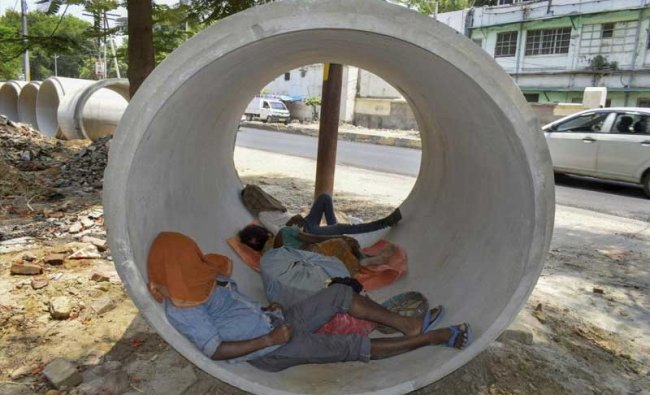 Allahabad: People sleep inside a concrete-pipe on a hot summer day, in Allahabad on Tuesday. (PTI Photo)