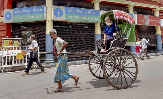 A hand rickshaw puller walks past a closed bank ATM on the second day of the two-day nationwide strike called by the United Forum of Bank Unions (UFBU) to press for wage revision, in Kolkata, Thursday, May 31, 2018. (PTI Photo/Ashok Bhaumik)