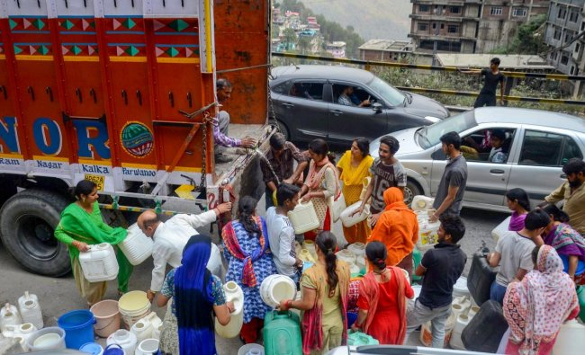 Shimla: People gather around a truck to collect water, as the city faces acute shortage of drinking water, in Shimla on Wednesday, May 30, 2018. (PTI Photo)