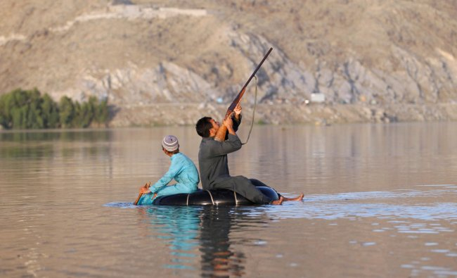 An Afghan hunter shoots at a duck in Laghman province, Afghanistan May 30, 2018.REUTERS/Parwiz