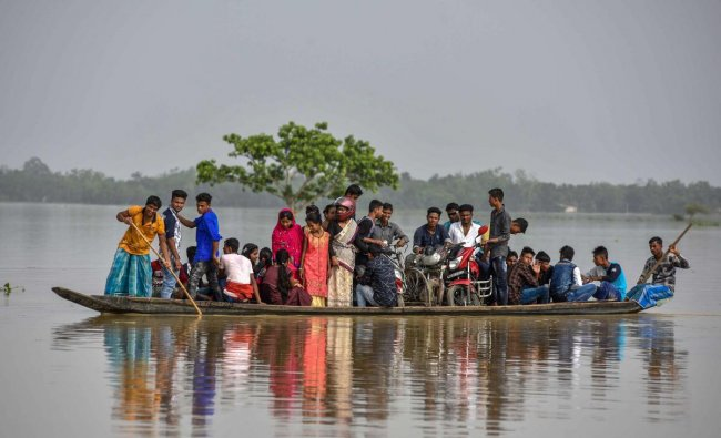 Villagers cross a flood-affected area on a boat, in Hojai on Saturday. PTI Photo