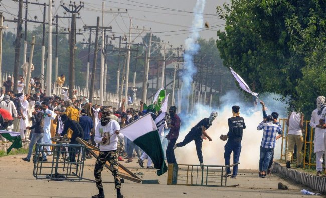 Protestors throw an exploded tear gas shell at police and CRPF personnel in retaliation during a clash, which erupted after youth staged a protest march soon after Eid-ul-Fitr prayers in Srinagar. PTI Photo