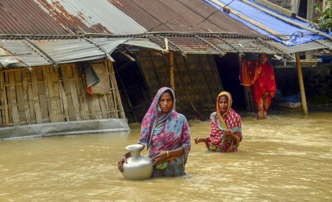 Villagers carry clean water as they wade across flood-affected areas at Nilambazar village, in Karimganj. PTI Photo