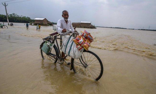 A man pushes his bicycle through flood water at Jamunamukh village in Hojai district of Assam. PTI Photo
