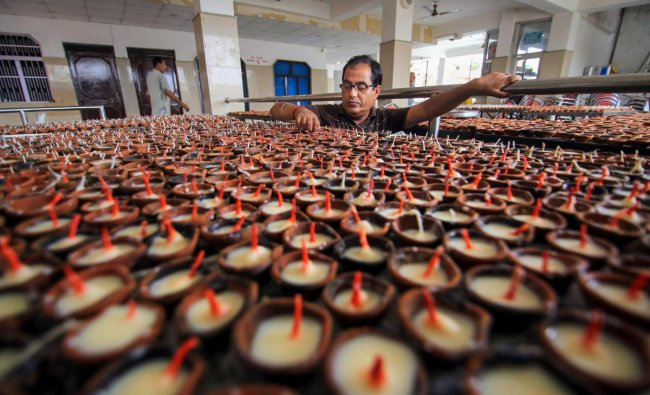 A person from the Kashmiri Pandit community arranges traditional earthern lamps at the replica of Kheer Bhawani temple, during preparations for \'Jyeshthaashtami\' annual congregation, in Jammu. PTI Photo