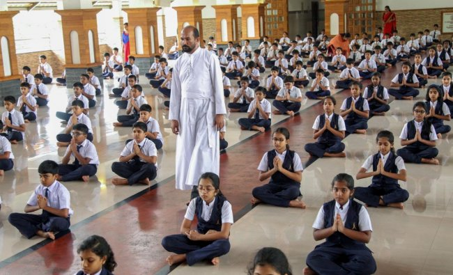 Students practice yoga on the eve of International Day of Yoga 2018, in Kozhikode. PTI Photo
