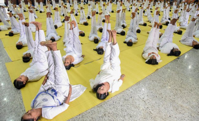Women practice yoga asana to mark the International Yoga Day organised by Pathanjali yoga training and research centre at Kochi. PTI Photo