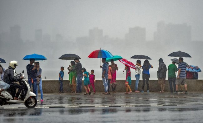 People enjoy in the rains at Marine Drive promenade in Mumbai on Saturday, June 23, 2018. PTI