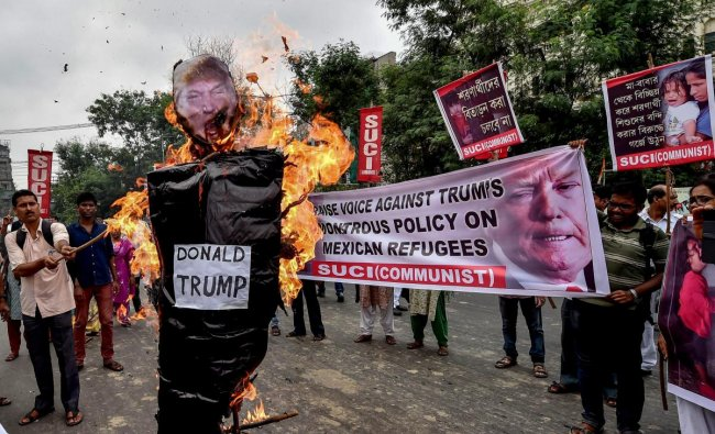 Socialist Unity Centre of India (SUCI) activists burn an effigy of the US President Donald Trump during a protest against Trump\'s inhuman treatment to Mexican refugees, in Kolkata on Saturday, June 23, 2018. PTI