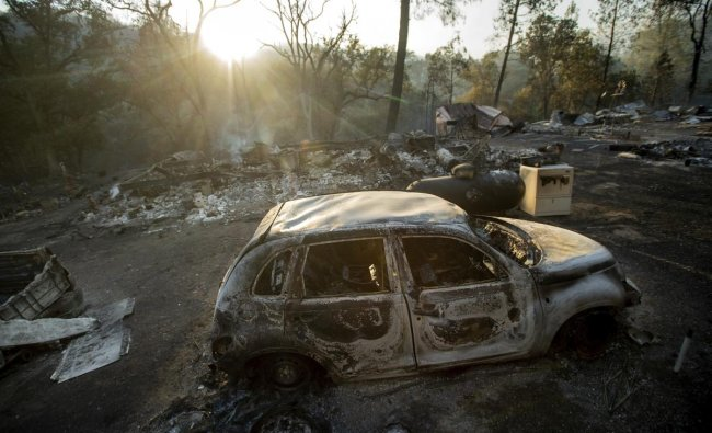 A vehicle scorched by a wildfire rests in a clearing on Wolf Creek Road near Clearlake Oaks, Calif., Sunday, June 24, 2018. Wind-driven wildfires destroyed buildings and threatened hundreds of others Sunday as they raced across dry brush in rural Northern California. AP/PTI