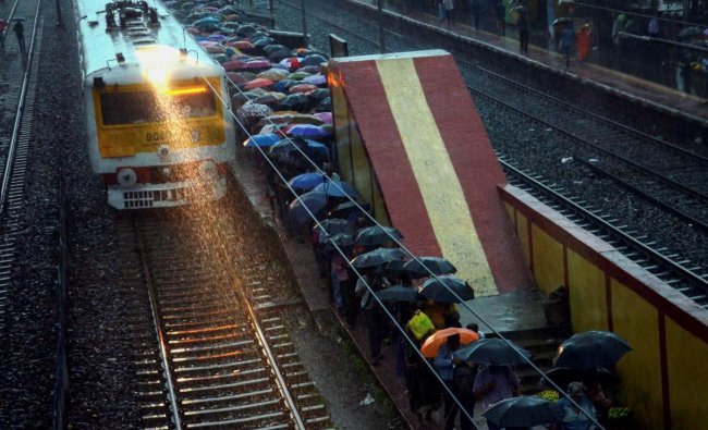 A local train makes way through heavy rains as passengers shield themselves under umbrella at a railway station, in Kolkata on Monday morning, June 25, 2018. PTI