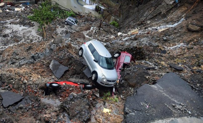 Several cars struck in debris after a wall collapsed at a construction site in Antop Hill, Wadala East area, in Mumbai on Monday, June 25, 2018. PTI