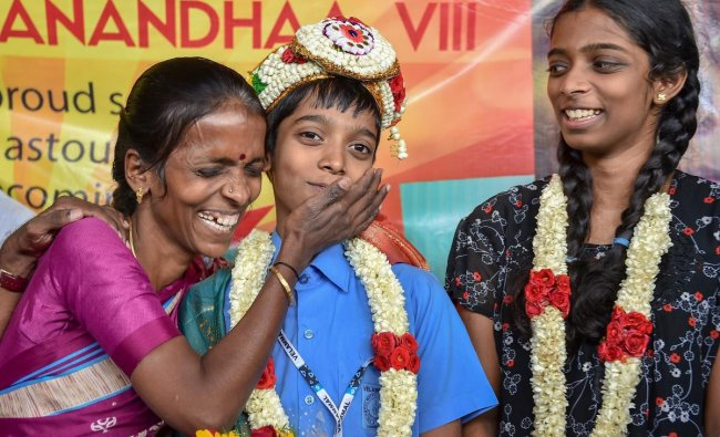 Indian Chess Grandmaster Rameshbabu Praggnanandhaa being greeted by his mother Nagalakshmi as his sister looks on, on his arrival, at Chennai Airport on Tuesday, June 26, 2018. Praggnanandhaa has become the country's youngest, and the world's second youngest, Chess Grandmaster at the age of 12 years. PTI