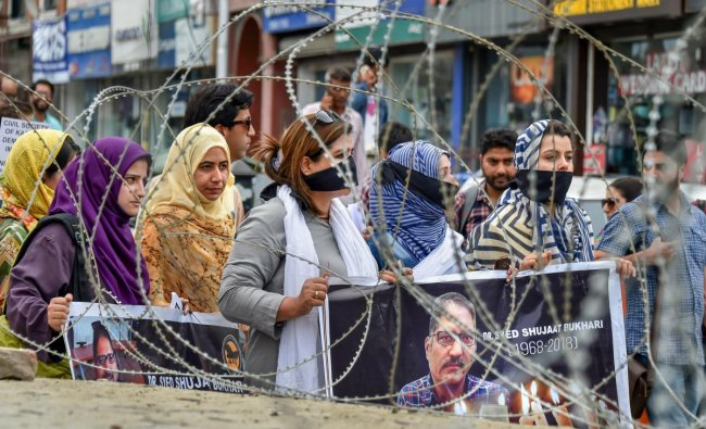 Journalists hold placards during a silent protest march against the killing of Rising Kashmir newspaper editor-in-chief Shujaat Bukhari, in Srinagar on Tuesday, June 26, 2018. PTI