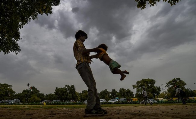 A young boy plays with a child as pre-monsoon clouds gather in the sky, in New Delhi, on Tuesday, June 26, 2018. PTI
