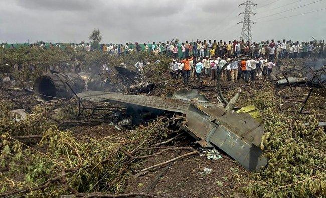 People gather near the debris of a Su-30 MKI fighter jet after it crashed at Wavi-Tushi village, near Nashik on Wednesday, June 27, 2018. PTI