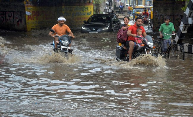 Commuters ride through a waterlogged street during heavy rainfall, in Mathura on Thursday, June 28, 2018. PTI