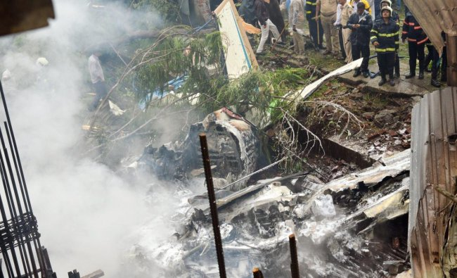 Firemen stand-by as they try to douse the smouldering remains of the chartered plane that crashed in Ghatkopar\'s Jivdaya Lane, killing 5, in Mumbai on Thursday, June 28, 2018. PTI