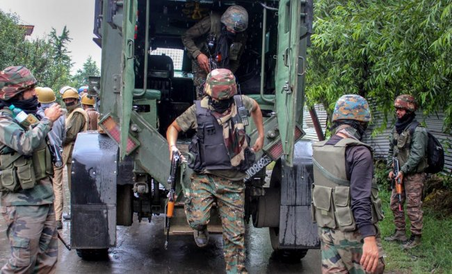 Security personnel outside the house which was held up by alleged militants during an encounter, in Pulwama district of south Kashmir on Friday, June 29, 2018. At least four persons were injured in clashes between stone-pelters and security forces today near an encounter site in Pulwama district where three alleged militants were reportedly trapped. Security forces launched a cordon and search operation in Thumna village after getting information about the presence of militants. (PTI Photo)
