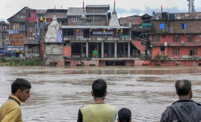 People look at the sumberged Hanumaan Mandir, in Srinagar on Saturday, June 30, 2018. As the rains continue to fall in the Valley, flood alerts have been issued to Srinagar\'s low lying areas by the authorities. (PTI Photo)
