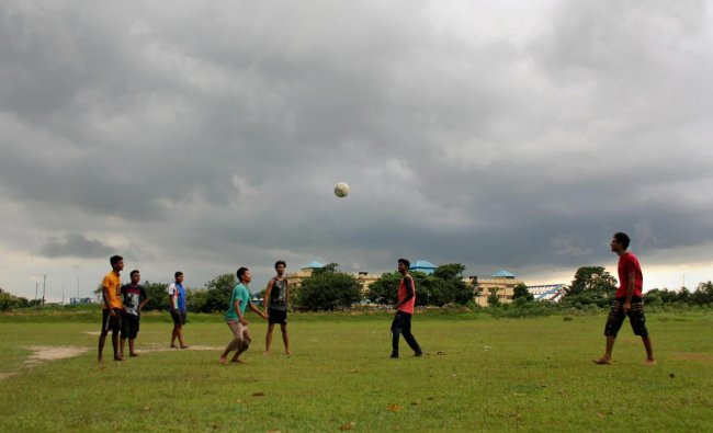 Youth play football as monsoon clouds hover in the sky at Balurghat in South Dinajpur district of West Bengal on Friday, June 29, 2018. (PTI Photo)