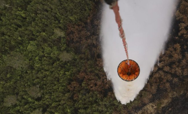 A helicopter drops water to extinguish a forest fire in Pali, South Sumatra, Indonesia. (AP/PTI Photo)