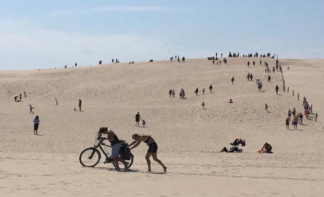 Women push a bike on the sand dunes in Slowinski National Park near Leba, Poland. (Reuters Photo)