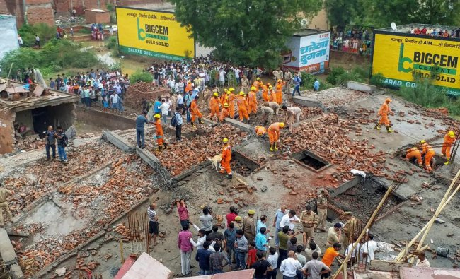Members of the National Disaster Response Force (NDRF) conduct a rescue operation after a four-storey building collapsed in Ghaziabad, Uttar Pradesh. (PTI Photo)