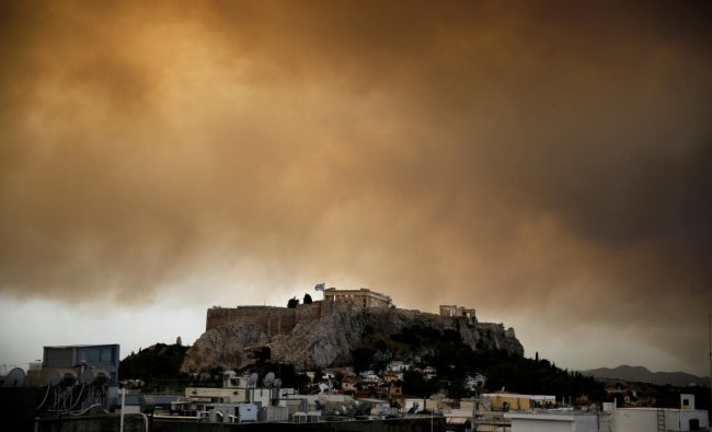Smoke from a wildfire burning outside Athens is seen over the Parthenon temple atop the Acropolis hill in Athens, Greece. (Reuters Photo)