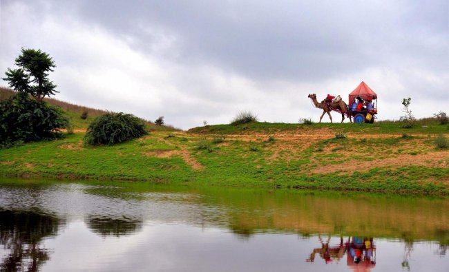 Tourists ride a camel-cart on a cloudy day, in Pushkar, Rajasthan. (PTI Photo)