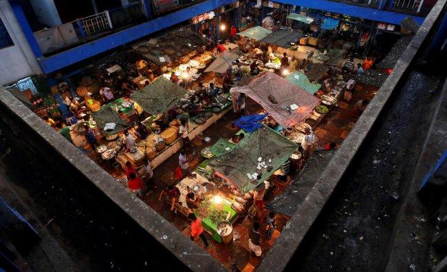 Vendors sell fish at a retail fish market in Kolkata. (Reuters Photo)