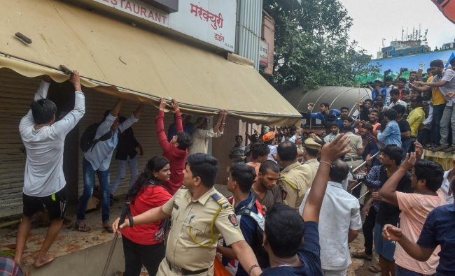 Police personnel lathi charge Maratha Kranti Morcha protesters who were vandalising store fronts during their statewide bandh, called for reservations in jobs and education protesters, in Thane. (PTI Photo)